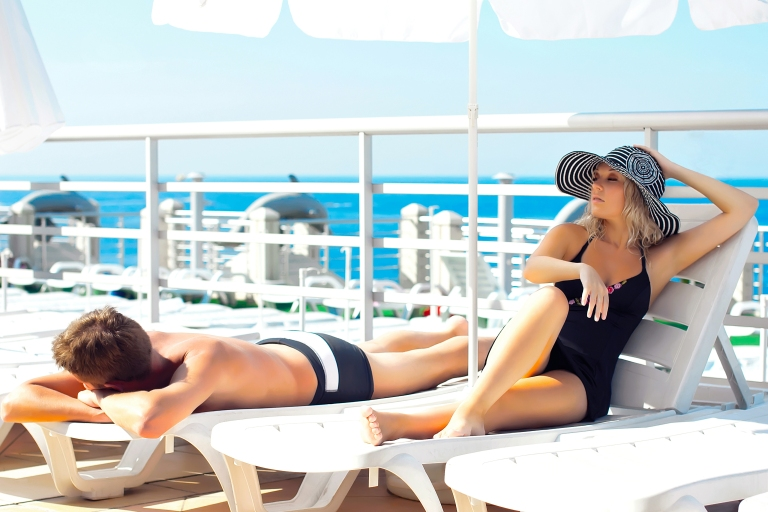 Man-and-woman-lying-on-chaise-lounges-on-cruise