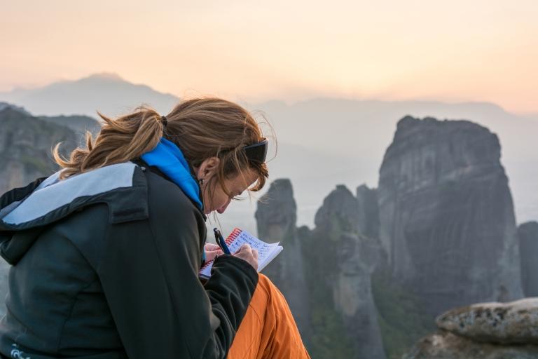 woman-traveler-writing-travel-journal-sitting-mountain-solo.jpg