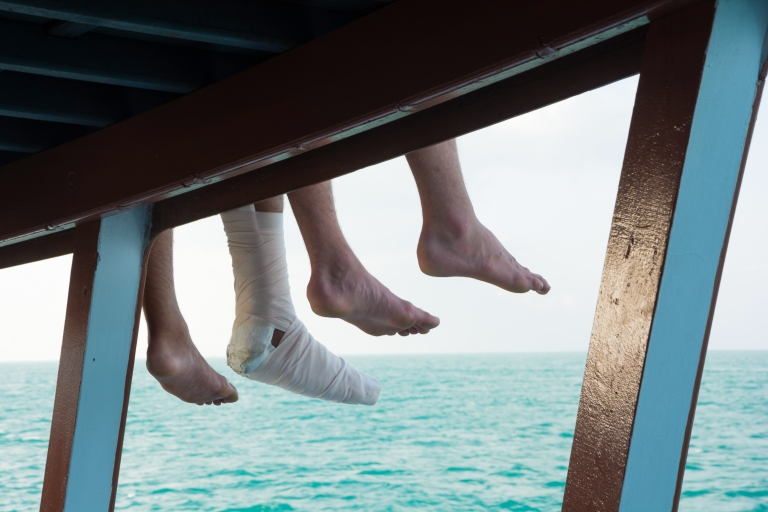 travel-accident-cast-travel-insurance-feet-dangling-water.jpg