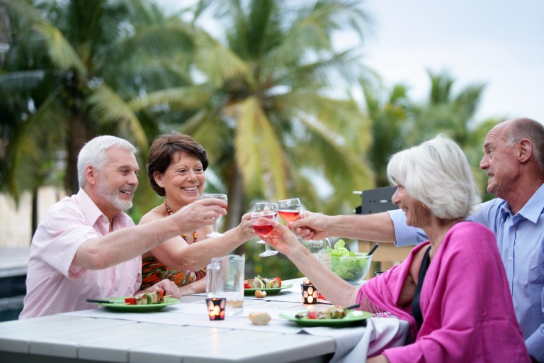 senior_group_enjoying_vacation_bbq_cheers_cocktails_mature_couples